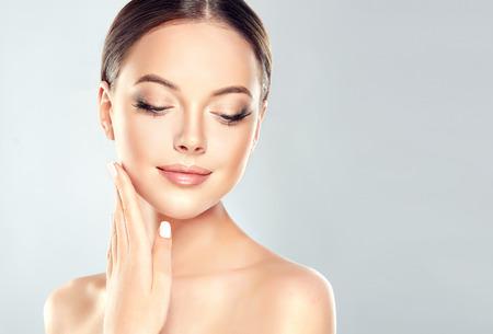 Hermosa mujer joven con piel limpia fresca toque cara propia. Tratamiento facial . Cosmetología, belleza y spa.