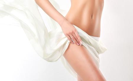 cuerpo humano: Delgado mujer bronceada cuerpo perfecto. Delgado joven cuerpo tonificado de la chica. Un ejemplo para los deportes y la aptitud de la cirugía plástica o estética y cosmetología.