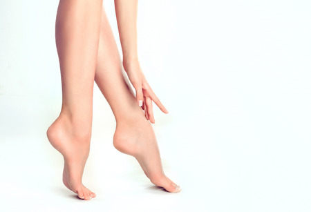 Perfect womans fingers with colorless manicure touch well-groomed feet.Spa ,scrub and foot care.