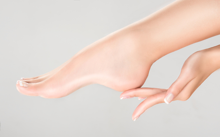 Perfect womans fingers with colorless manicure touch well-groomed foot.Spa ,scrub and feet care.