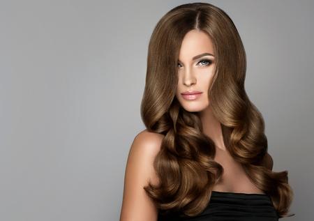 Brunette fille avec de longs et brillants cheveux ondulés. Beau modèle avec coiffure bouclée. Banque d'images