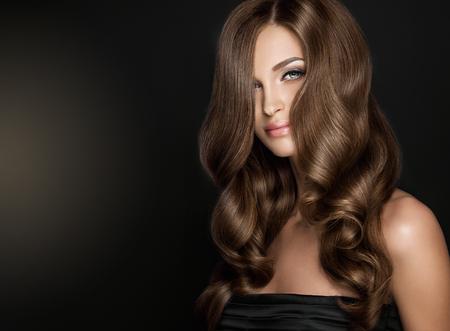 Brunette fille avec de longs et brillants cheveux ondulés. Beau modèle avec coiffure bouclée. Banque d'images - 74087062