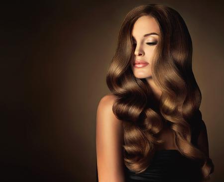 cabello rizado: chica morena con una larga y brillante pelo ondulado. Modelo hermoso con el peinado rizado.