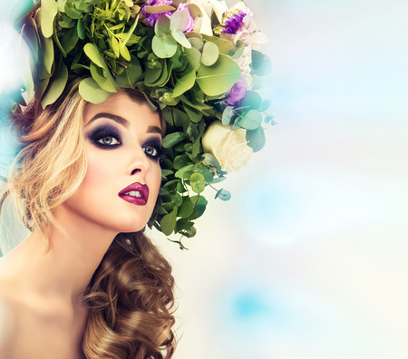 flower head: Lady Spring. Beautiful woman model with flower wreath on his head and makeup-smoky eyes style on the blurred background.