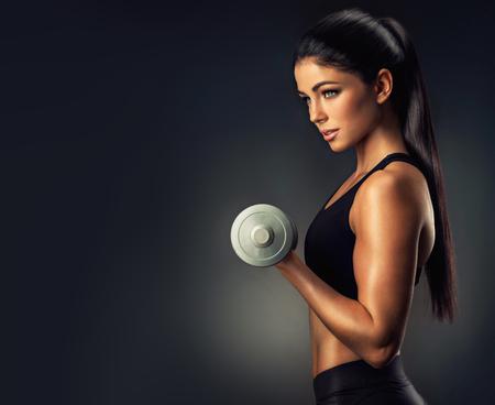 Mooie fitness vrouw opheffing van een halters. Fitness, sport, powerlifting en gym.Athletic vrouw die haar goed getraind lichaam.
