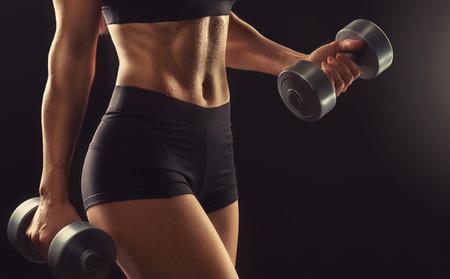 Athletische, gut ausgebildete Womens Körper mit Hanteln in den Händen. Workout-Konzept.Fitness, Sport, Powerlifting und Fitnessraum. Standard-Bild
