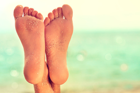 Perfect,clean,well cared  female feet with golden sand and azure south sea on background.Spa, scrub,  foot care and foot massage . Stock Photo