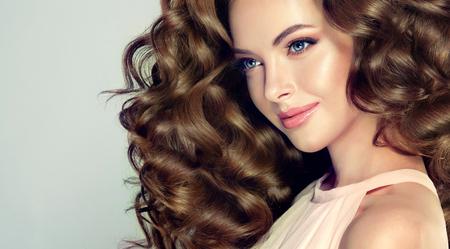 Bela modelo com penteado ondulado, denso e exuberante, sorriso atraente e terno nos lábios. Mulher morena com cabelo longo cacheado. Foto de archivo