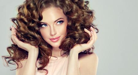 Modelo hermoso con el ondulado, peinado densa y exuberante, atractivo y tierna sonrisa en los labios. mujer morena con el pelo largo y rizado. Foto de archivo - 74950276