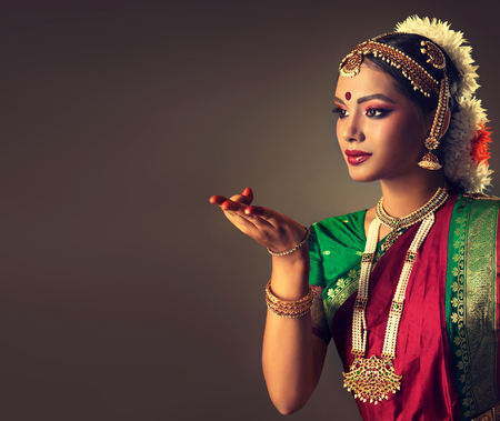 Beautiful girl-dancer of Indian classical dance bharatanatyam, dressed in traditional oriental dance suit, demonstrate gestures of folk dance. Culture and traditions of India.