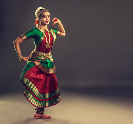 Beautiful girl-dancer of Indian classical dance bharatanatyam, dressed in traditional oriental dance suit, demonstrate gestures of folk dance. Culture and traditions of India. Фото со стока - 74607655