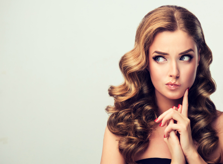 Young blonde haired model with a puzzled facial expression. Doubt  on the face of a woman.Well groomed blond hair and bright red make up and manicure. Image in Pin Up style. Фото со стока