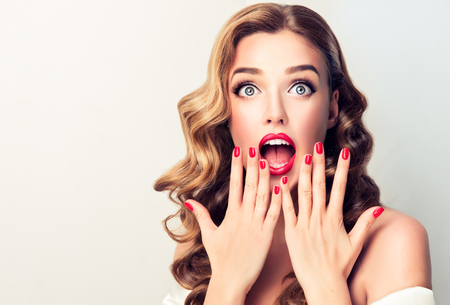 Extremely astonished and excited young blonde haired model  with wide opened mouth, is looking up above. Shock from happines.Well groomed blond hair and bright red make up and manicure. Image in Pin Up style.