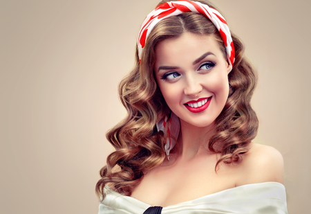 Young blond model with wide and  toothy smile and polka dot kerchief on the head is looking aside.Well groomed blond hair and bright red make up and manicure. Image in