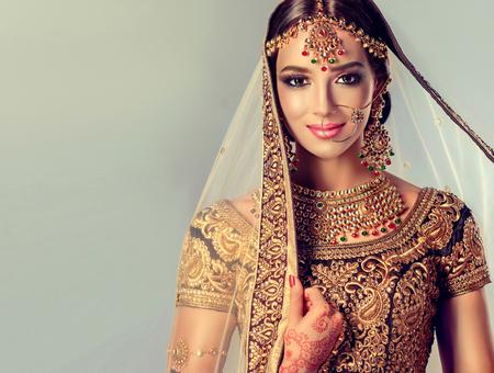 hinduismo: Modelo atractivo joven vestido en traje elegante, gildet, indio y joyería del estilo de Kundan. Traje tradicional indio lehenga choli.