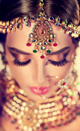 Set of jewelry in traditional indian style-kundan, put on the head and neck of young model. Bright and stylish make up on her face. Veiw from above.