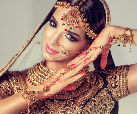 Young attractive model dressed in posh, gildet, indian costume, Kundan style jewelryand henna tatoo on the hands.  Traditional Indian costume lehenga choli.