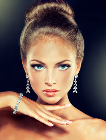 Young charming woman-model, with a hair gathered in a bun and dressed in modern, fashionable jewelry. Examples of different designs for beads, bracelets and earings.