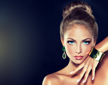 Young charming woman-model, with a hair gathered in a bun and dressed in modern, fashionable jewelry. Examples of different designs for beads, bracelets and earings. Imagens