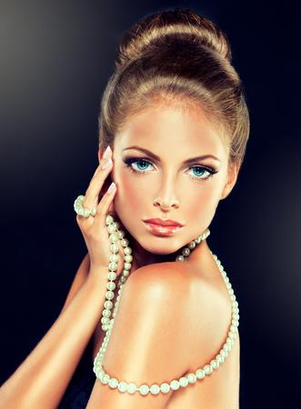 젊은 매력적인 여자 - 모델, 머리에 롤빵에 모여 및 현대, 유행 보석 옷. 구슬, 팔찌 및 earings에 대한 다른 디자인의 예.