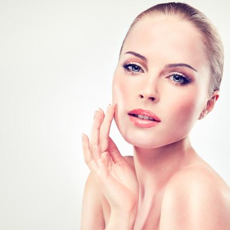 Mooie, jonge, blondeharige vrouw met schone, frisse huid raakt het gezicht aan. Gezichtsbehandeling, cosmetologie, schoonheidstechnologie en spa. Stockfoto