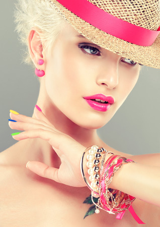 Stylish blonde girl in a straw hat with bright pink makeup and earrings-beads, multicolored nail polish on her nails.Spring and summer look. Stok Fotoğraf