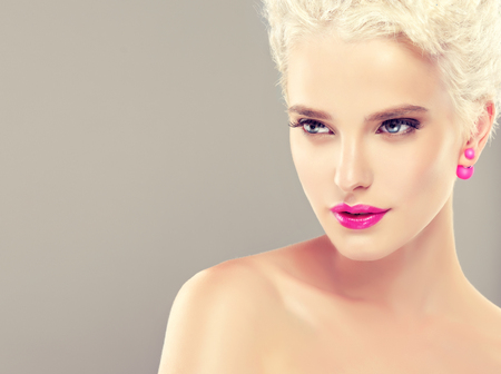 cabello corto: Young appealing woman with blond hair and man-style short haircut.Bright pink makeup and earrings-beads.