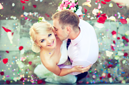 Happy young just married couple surrounded by petals scattered under them feet. Groom hugs his bride and kissing her neck. Idyllic moment of happiness.