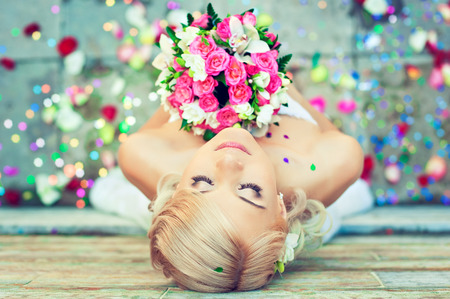 Beautiful blonde new married bride is holding wedding  bouquet of flowers, surrounded by petals scattered under her feet. Idyllic moment of happiness. Look from above. Stock Photo