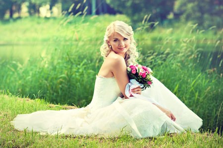 Beautiful blonde new married bride dressed in a wedding gown, with happy smile on the face, is sitting on the green grass in front of verdurous pond.