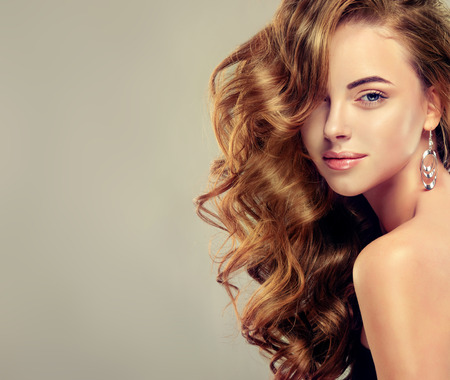 Jonge bruine haired vrouw met volumineus, glanzend en golvend haar. Mooi model met lang, dik en krullend haarstijl.