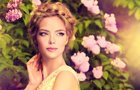 Beautiful young model in a spring blossomed garden.Variant of fashionable hairstyle, disheveled braid wrapped around the head.