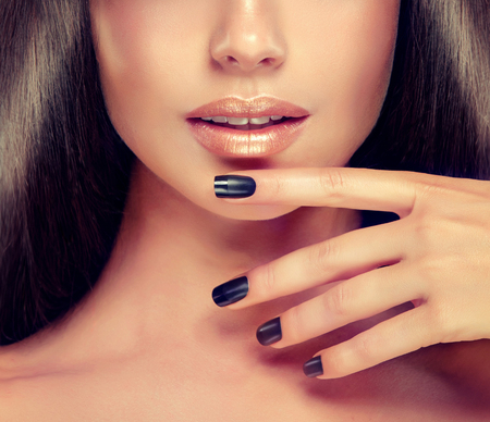 Beautiful woman-model is showing black french style manicure on the nails and peach color lipstick . Makeup and cosmetic. 版權商用圖片