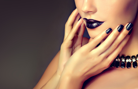 Beautiful woman-model is showing black french style manicure on the nails and black lipstick . Makeup and cosmetic.