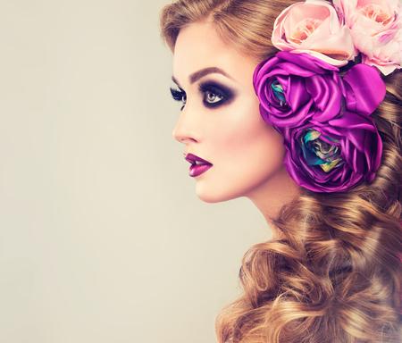 그녀의 금발 조밀 한 둥근 헤어 스타일에 큰 보라색과 흰색 꽃과 아름다운 모델. 메이크업 연기가 자욱한 눈. 유행 메이크업 및 머리 장식 여름 소녀입
