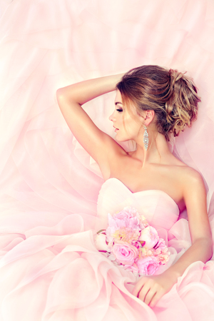 Fashionable bride in gorgeous and posh wedding gown with wedding bouquet of flowers. Perfect wedding hairstyle for long hair, luxurious bridal jewelry and outfit.