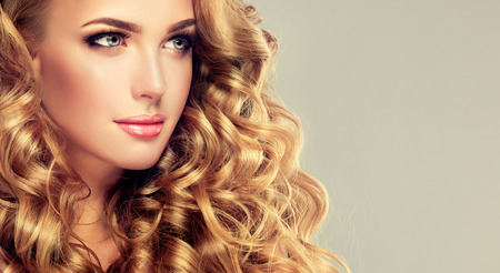 Young, blonde haired woman  with voluminous, shiny and wavy hair. Beautiful model with long, dense and curly hairstyle, vivid make-up.