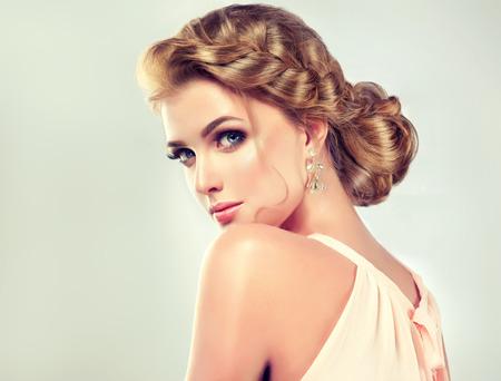 膨大な光沢のある、波状毛との若い、ブロンドの髪の女性。おしゃれなエレガントな結婚式のヘアスタイル、鮮やかな化粧と髪に淡いバラの美しい