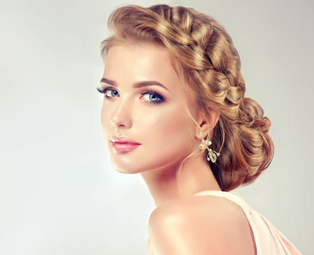 Young, blonde haired woman  with voluminous, shiny and wavy hair. Beautiful  woman with fashionable elegant wedding hairstyle, vivid make-up and pale roses on hair. Banco de Imagens - 79188663