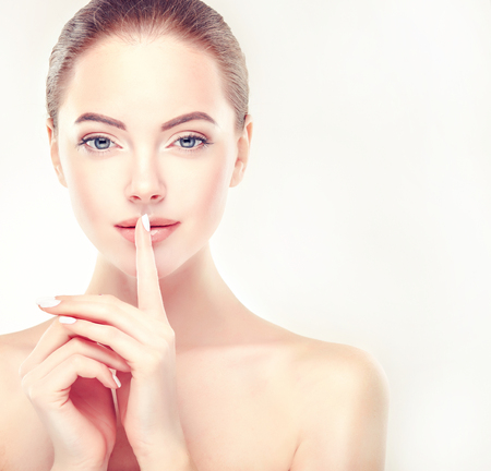 Beautiful, young, brown haired woman with clean fresh skin is holding a finger in front of lips. Symbol of women secrets. Facial treatment, cosmetology. Imagens