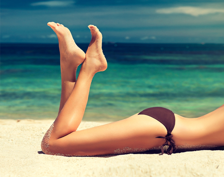 moisturize: Young, attractive woman is lying on the beach sand.Tanned well-groomed feet amid tropical turquoise sea. Pedicure and foot Spa.