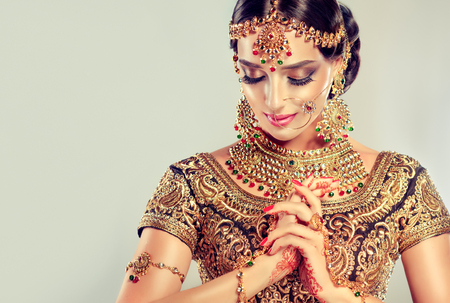 Young attractive model dressed in posh, gildet, indian costume and Kundan style jewelry. Traditional Indian costume lehenga choli. 스톡 콘텐츠