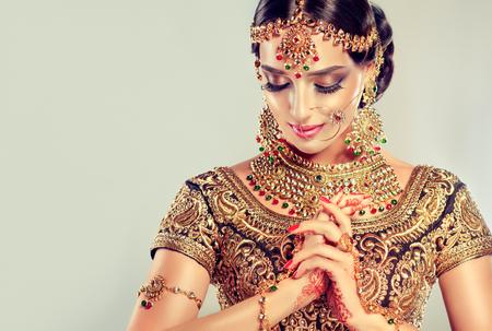 Jeune modèle attrayant habillé en chic, gildet, costume indien et bijoux de style Kundan. Costume traditionnel indien lehenga choli. Banque d'images - 80017590