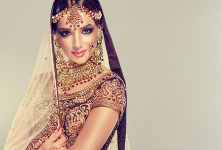 Jong aantrekkelijk gekleed model in elegant, gildet, Indisch kostuum en Kundan-stijljuwelen. Traditionele Indische leoli van kostuumchenga.