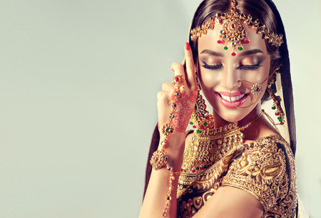 Young attractive model dressed in posh, gildet, indian costume and Kundan style jewelry. Traditional Indian costume lehenga choli. Banco de Imagens
