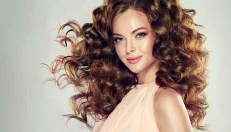 Beautiful model with wavy, dense and lush hairstyle, attractive and tender smile on her lips. Brunette woman with long curly hair.