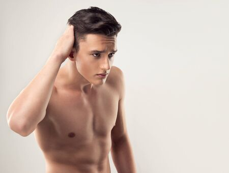 Young handsome man with trendy hairstyle and bare torso is touching his hair and looking at invisible mirror.