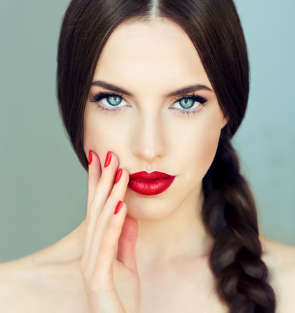 Close up portrait of beautiful  young brunette woman-model  with  long braided hair. Pigtail hairstyle. Bright blue eyes, red lipstick on the lips and red  manicure on the nails.