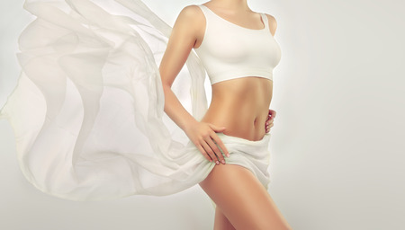 Slim and perfect white skinned woman body . Slim toned young female body. An example of slender figure for sport, fitness or plastic surgery and esthetic cosmetology.