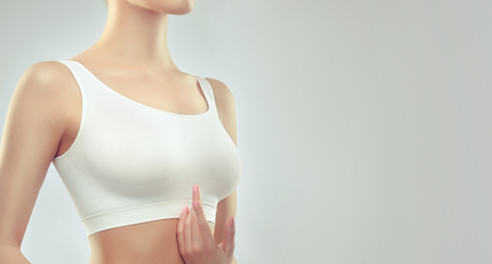 White top on the attractive, well shaped woman breast. An example of slender figure for sport, fitness or plastic surgery and esthetic cosmetology. Stockfoto